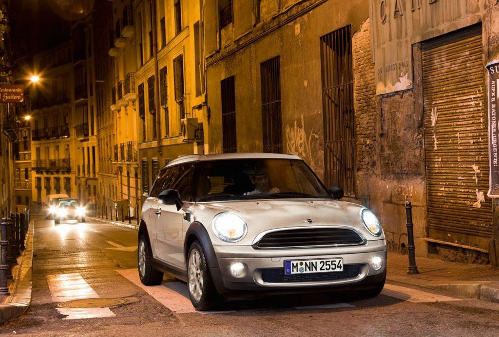 A white Mini Clubman drives down an urban street at night