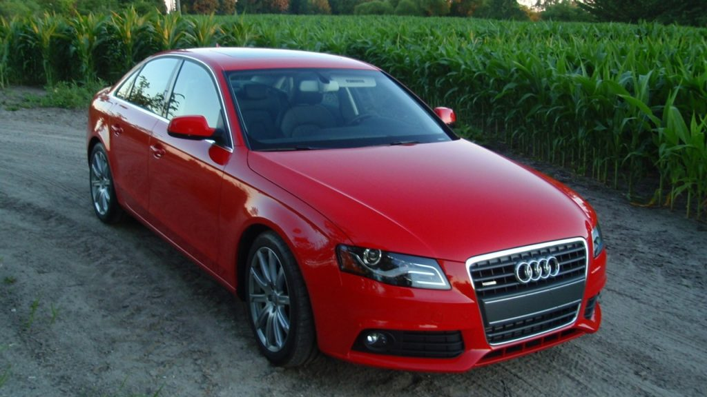 A red Audi sedan sits on a road by hedges