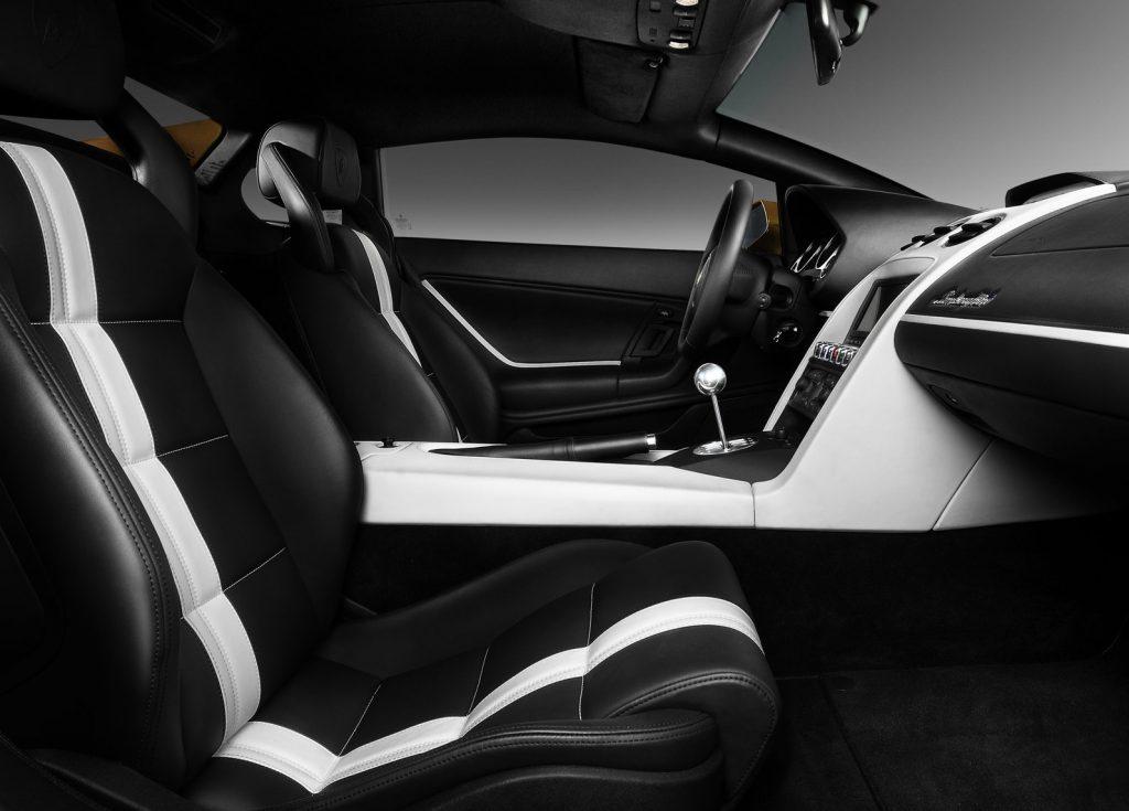 Interior shot of the 2010 Lamborghini Gallardo LP550-2 Valentino Balboni, showing white-striped black leather seats, white center console, and gated manual shifter