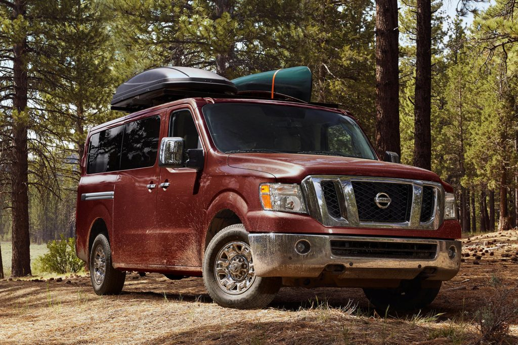 a dark red Nissan NV driving off road in the forest with recreational gear loaded up top