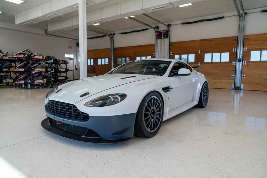 White 2013 Aston Martin V8 Vantage GT4 with blue bumper sitting in garage