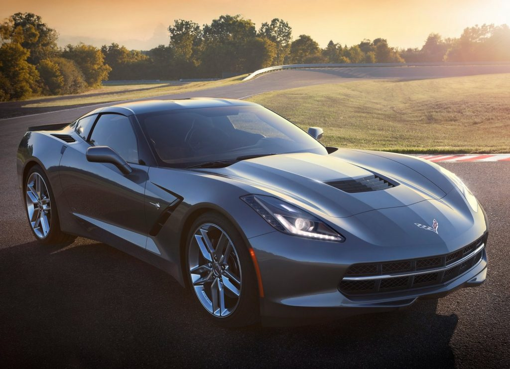 Gray 2014 C7 Chevrolet Corvette Stingray parked on a racetrack in front of a rising sun