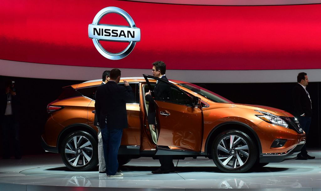People discuss a Nissan 2015 Murano on display at the LA Auto Show's press and trade day