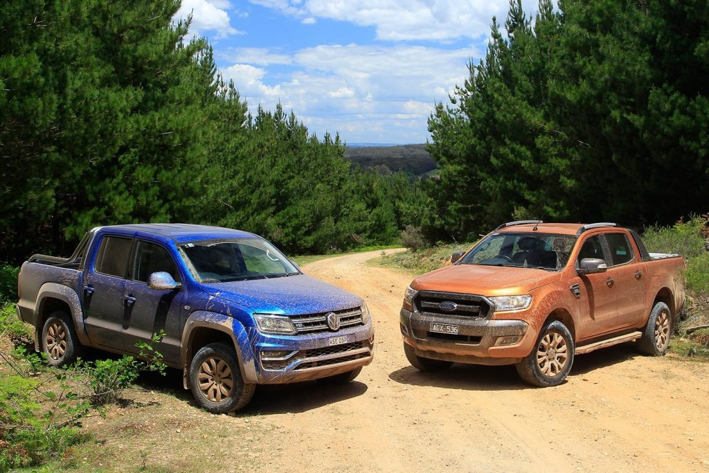 The Volkwagen Amarok and Ford Ranger are side by side on a dirt road