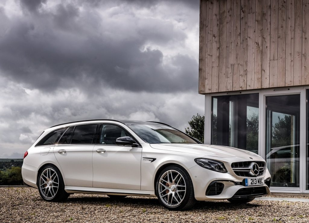 White 2018 Mercedes-AMG E63 S Wagon parked in front of a modernist house