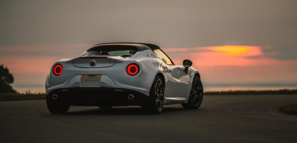 The rear of a white Alfa Romeo 4C convertible sits on the coast at sunset.