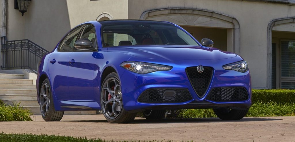 A blue Alfa Romeo Giulia sedan sits in a driveway.