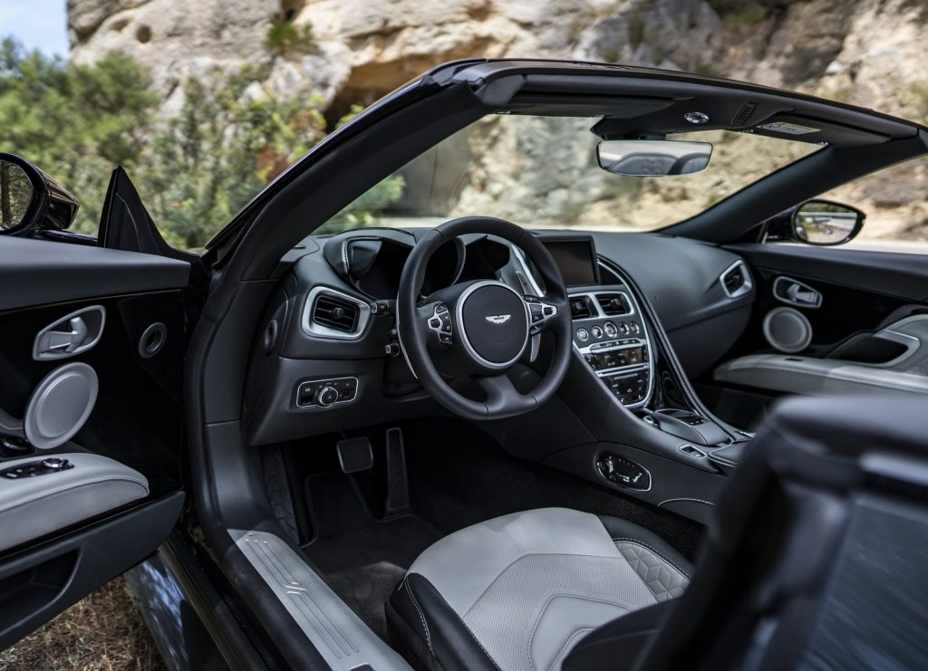 The 2020 Aston Martin DBS Superleggera Volante's front seats, dashboard, and center console, seen with the driver's door open