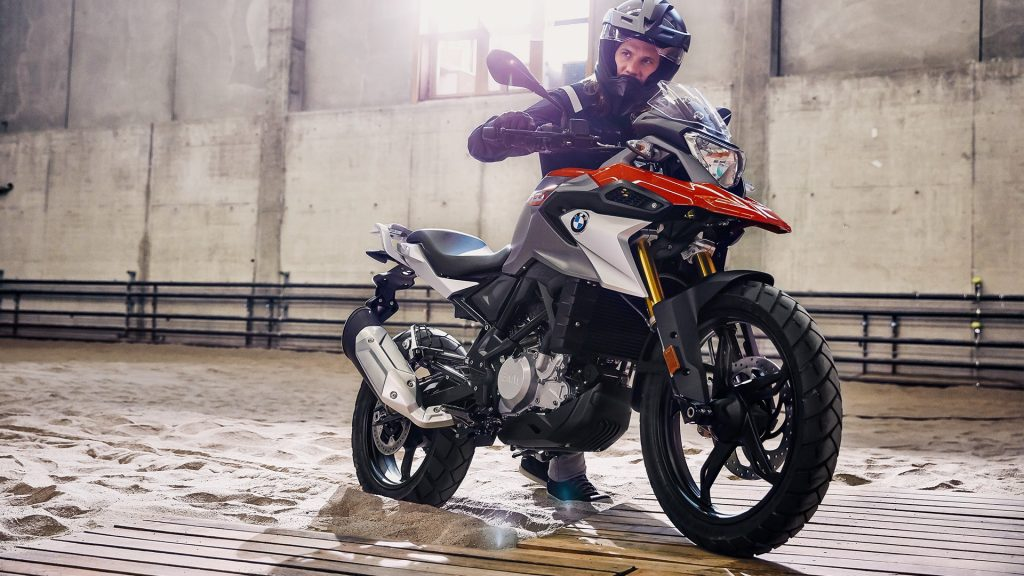 Red-and-silver 2020 BMW G 310 GS with rider standing in soft sand