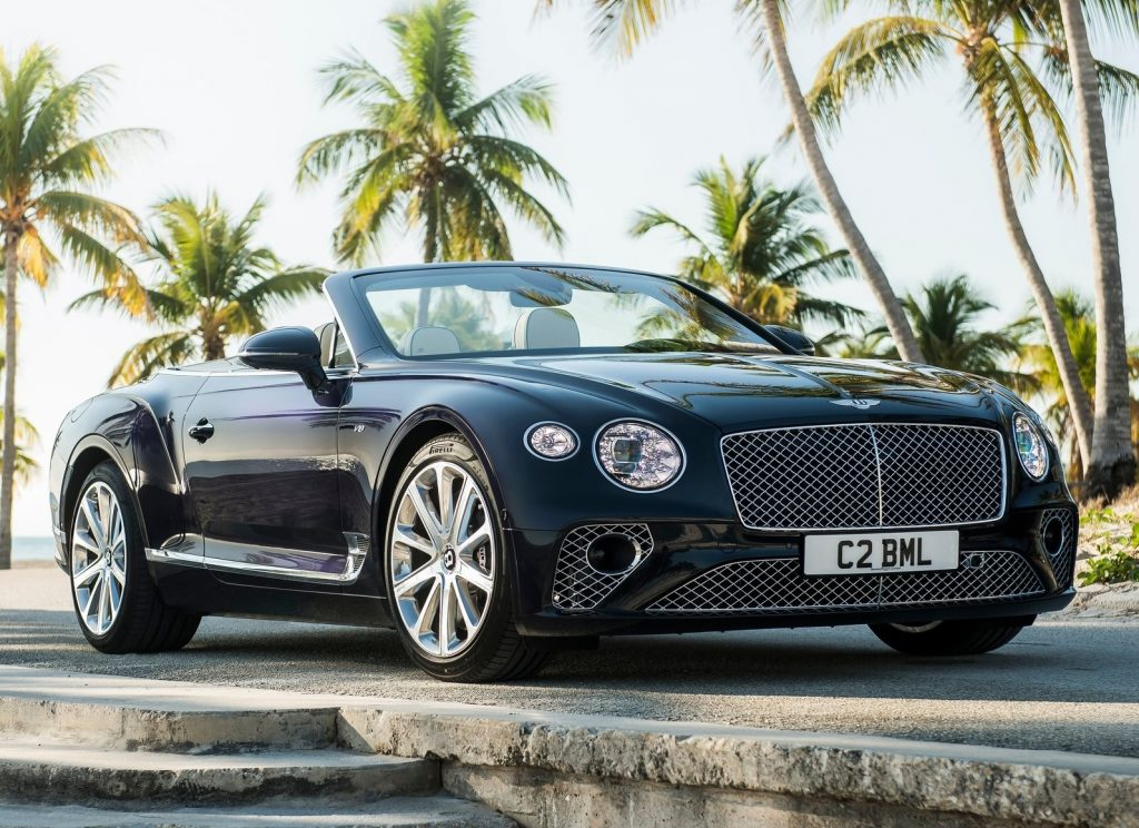 Black 2020 Bentley Continental GT V8 Convertible in front of palm trees with the roof down