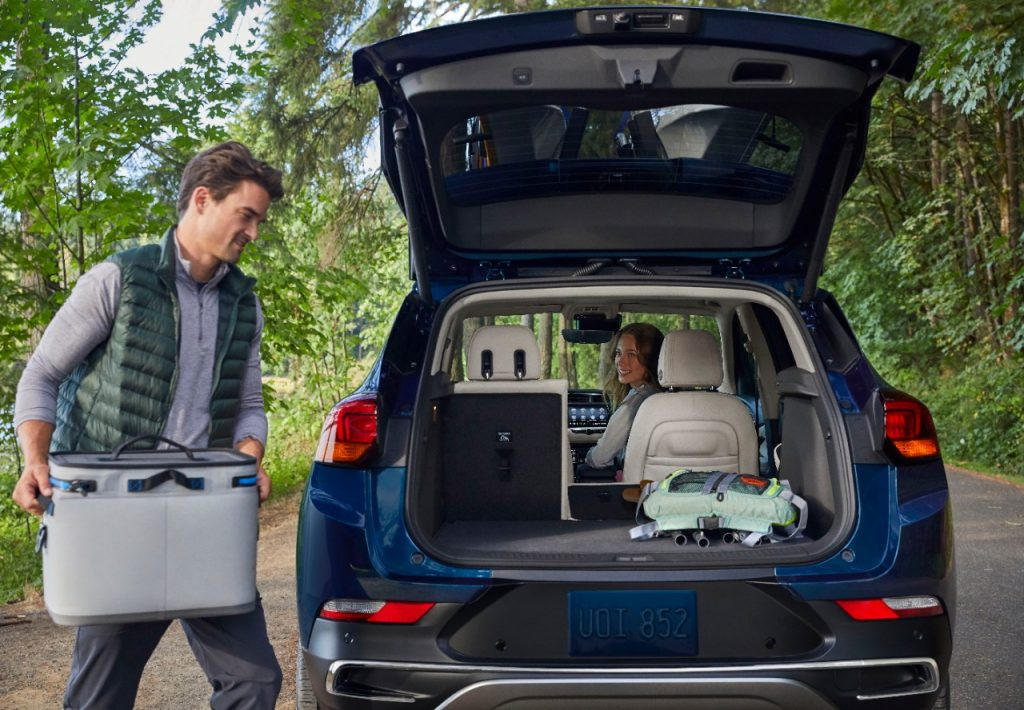 man loading up 2020 Buick Encore with camping supplies