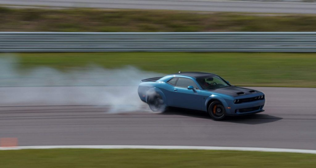 A blue 2020 Dodge Challenger drifts at the track
