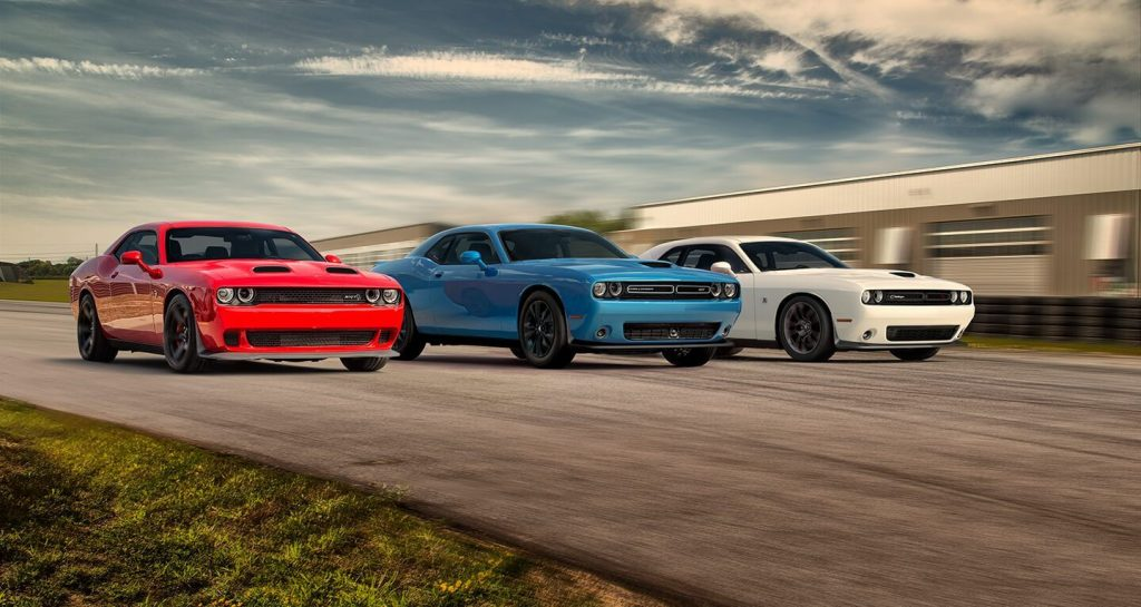 Three 2020 Dodge Challengers, red, white, and blue are on the track side by side.
