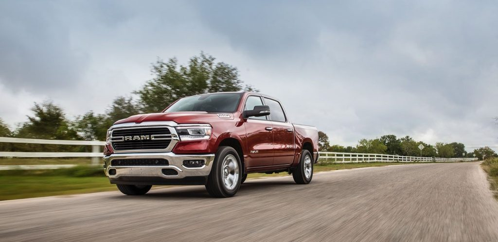 a new red Ram 1500 pickup truck driving through some farm land