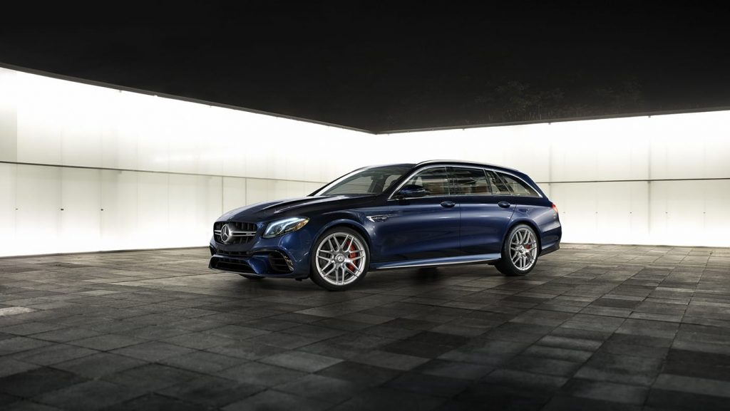 a blue Mercedes AMG wagon sits in a dark room with a backlit wall