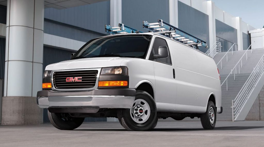 A white 2020 GMC Savana cargo van sits in front of a large commercial building