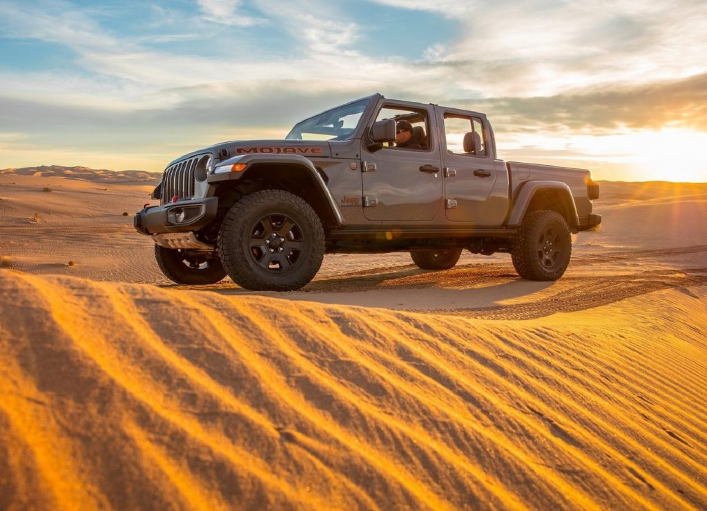 Grey-brown 2020 Jeep Gladiator Mojave truck crossing a dune at sunset