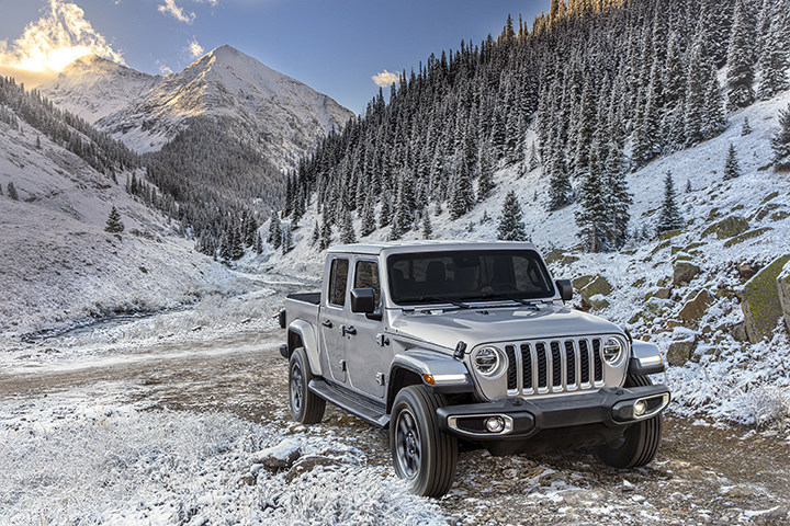 A Jeep Gladiator at the base of a snow covered mountain