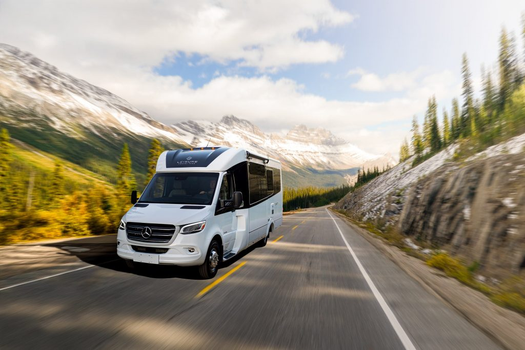 White 2020 Leisure Travel Vans Unity RV driving through a forested mountain road