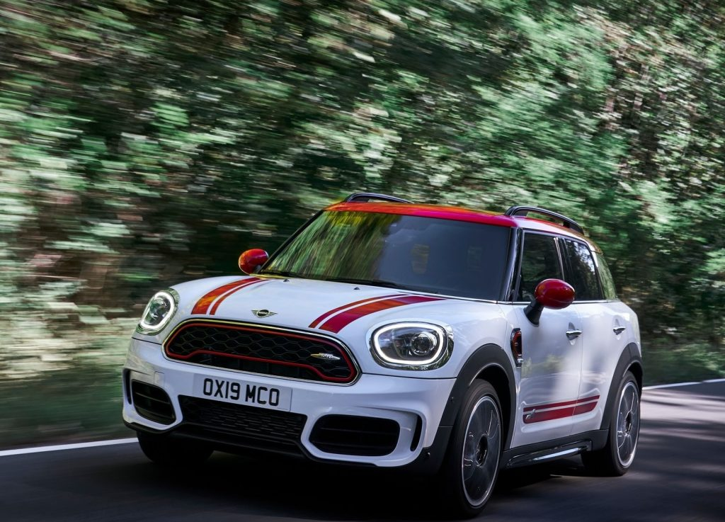 White-and-red-striped 2020 Mini Countryman John Cooper Works driving through a forest
