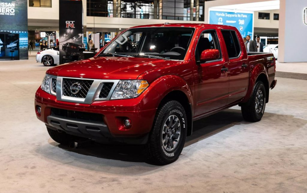A red 2020 Nissan Frontier pickup truck on display at a car show