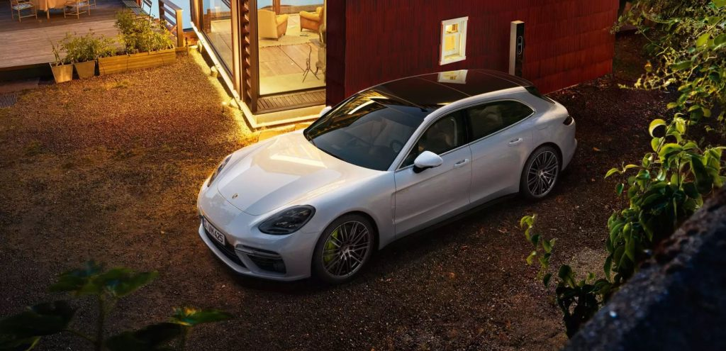 A white Porsche Panamera with a black top sits on a dirt driveway