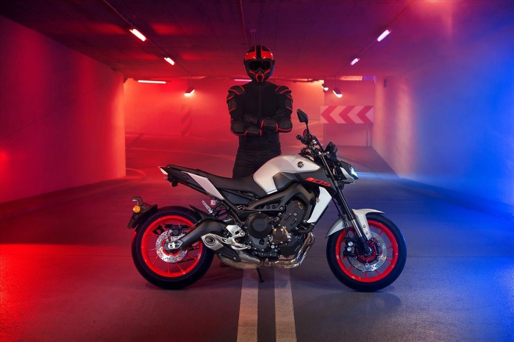 White 2020 Yamaha MT-09 standing in front of a blac-clad helmeted rider in a red-and-blue-lit tunnel