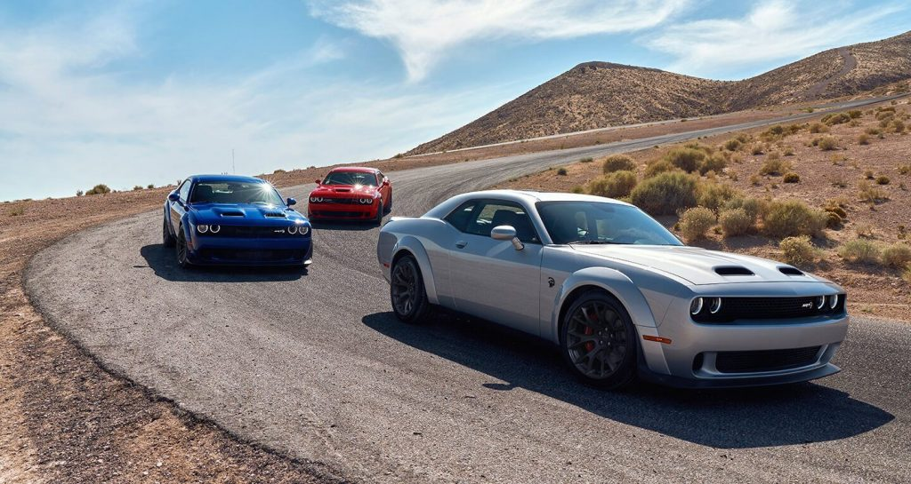 Three 2020 Dodge Challengers are on the track at the same turn together.