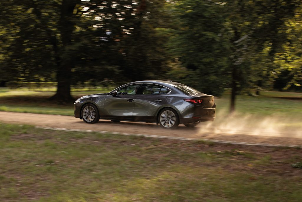 a gray Mazda3 Sedan in motion on a scenic dirt road is a newer model without current complaints