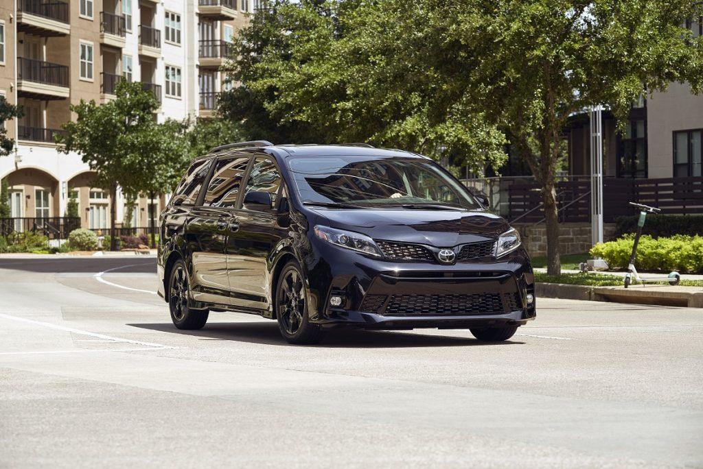 a black on black Toyota Sienna minivan cruising the neighborhood streets