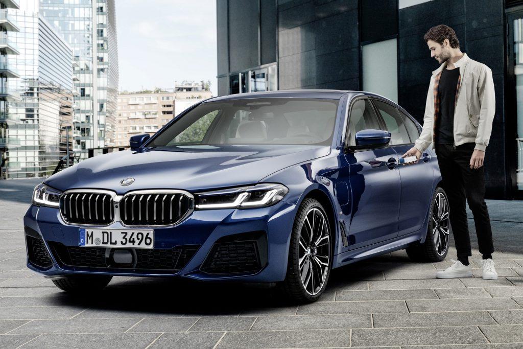 Unlocking a dark-blue 2021 BMW 5-Series sedan with an iPhone using Apple CarKey