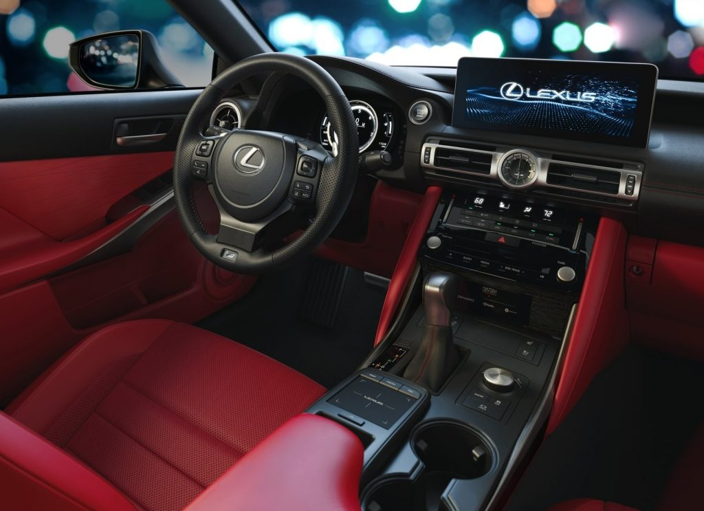 The 2021 Lexus IS 350 F Sport's interior, showing the red upholstery and center console trim, touchscreen, touchpad, and digital instrument cluster