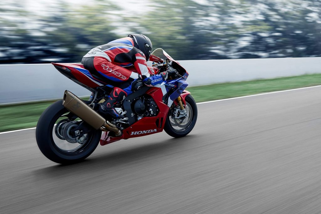 a red, white, and blue CBR1000RR-R sport bike racing down the street