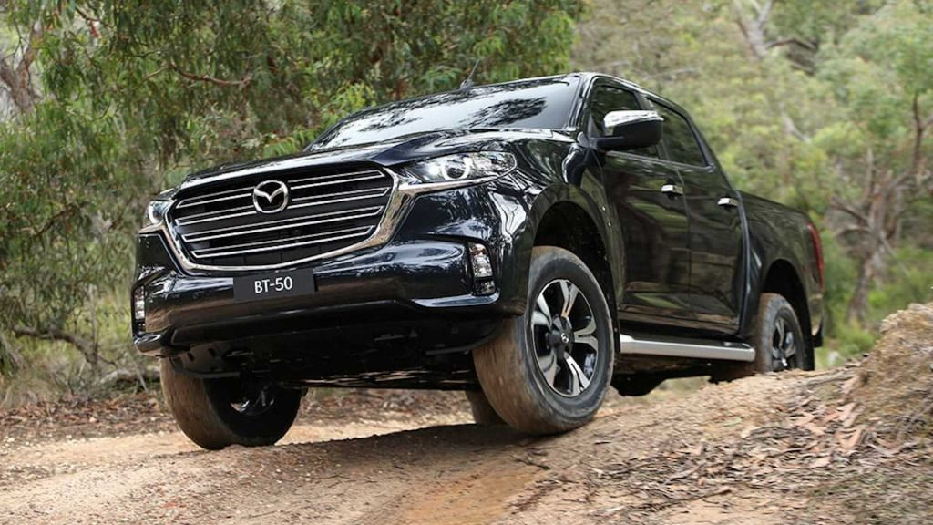 Black 2021 Mazda BT-50 pickup truck rising over a ridge