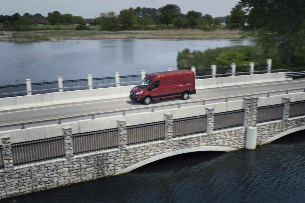 A red 2020 Ford Transit Cargo driving over a bridge