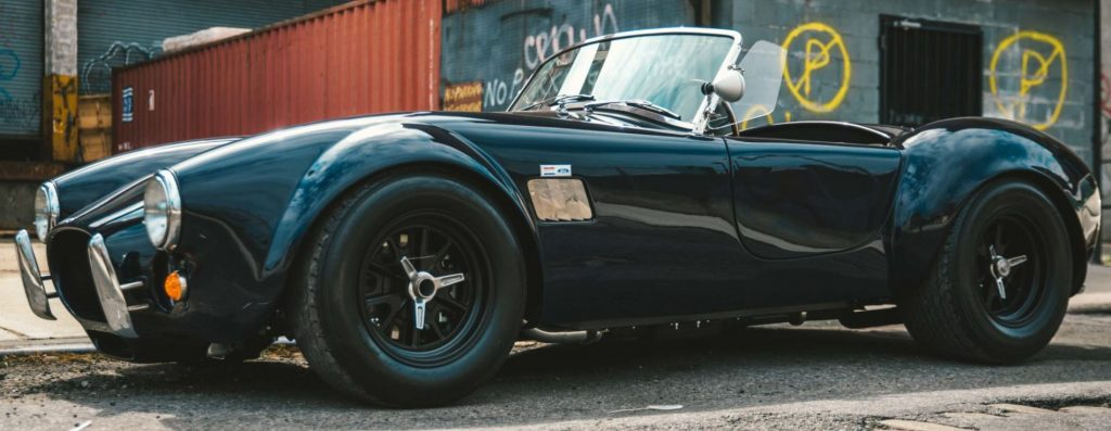 A black AC Shelby Cobra sits in an industrial area.