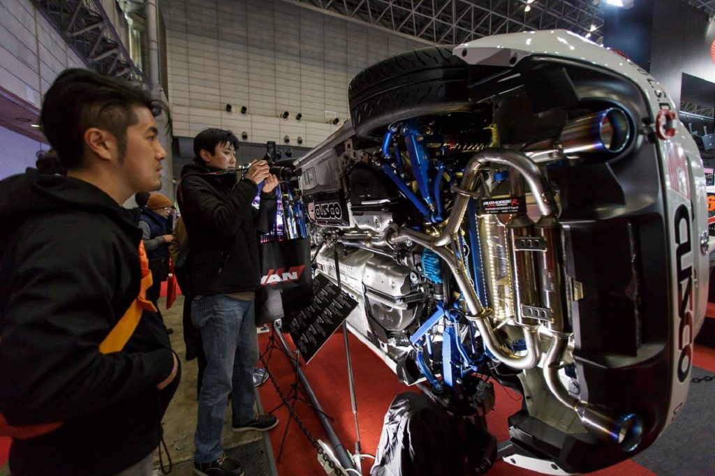 Visitors look at the aftermarket exhaust of a sideways-turned car