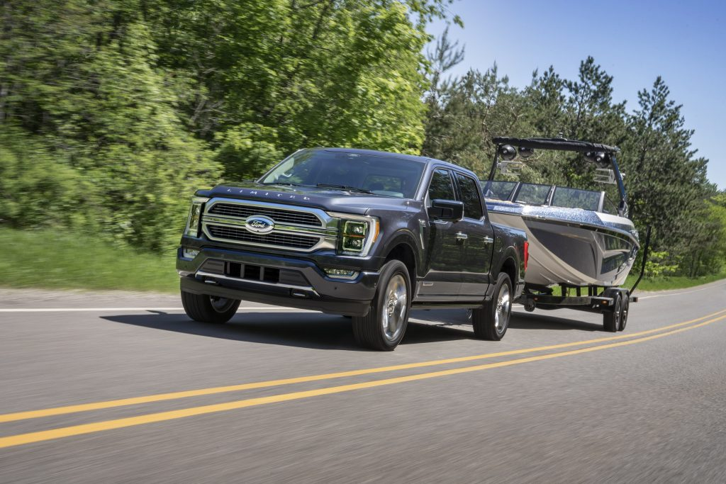 A gray 2021 Ford F-150 Hybrid towing a boat
