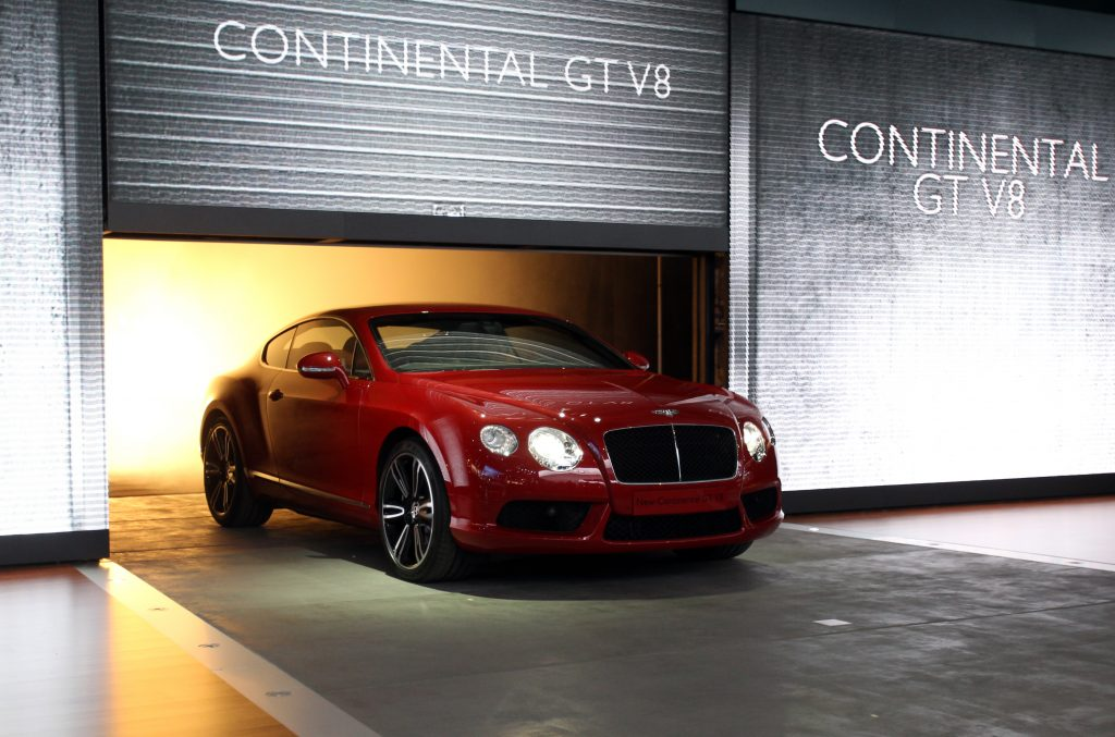 A red Bentley Continental GT V8 pulls under a backlit garage door