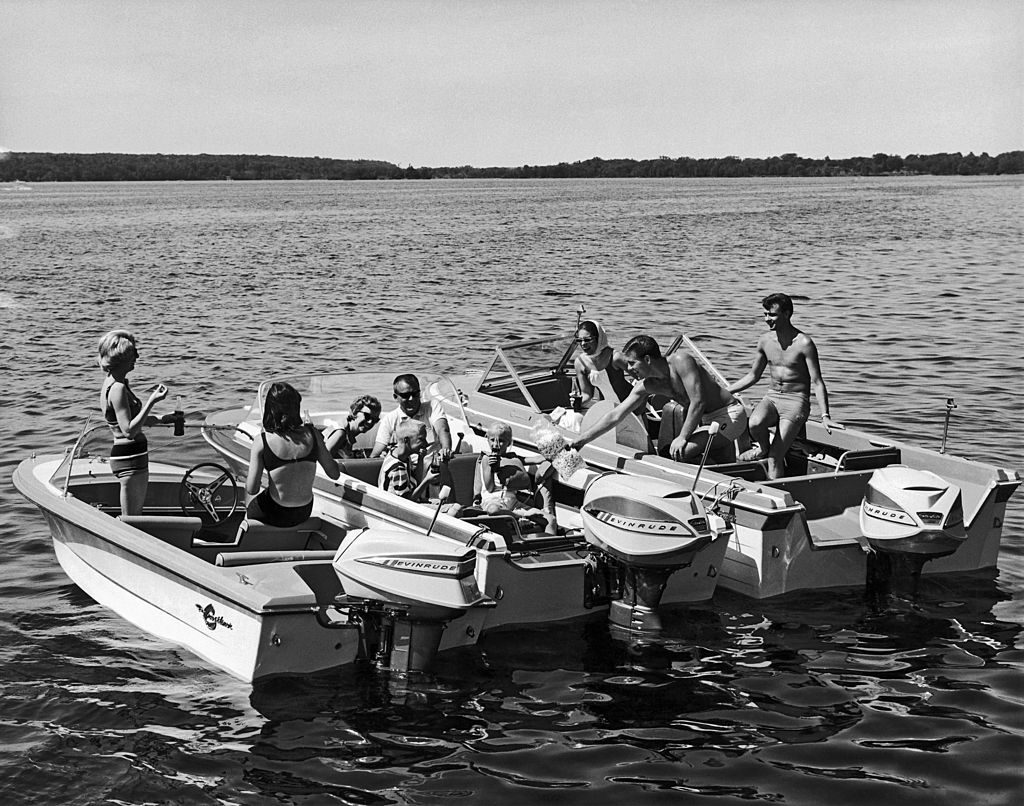 Three sets of boaters with Evinrude motors gather together on the lake to share food and drink, late 1950s or early 1960s. (Photo by Underwood Archives/Getty Images)