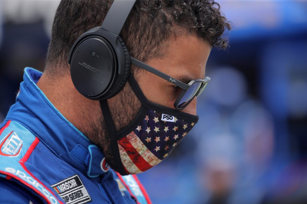 NASCAR driver Bubba Wallace stands with an American flag face mask, in his blue racing suit, with ear protection and sunglasses on