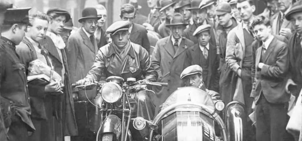 Black-and-white shot of Carlo Abarth seated on his motorcycle, with his co-driver in the sidecar, in front of a large crowd