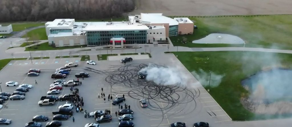 Tire burnouts and donuts are clearly visible in the markings of a church parking lot