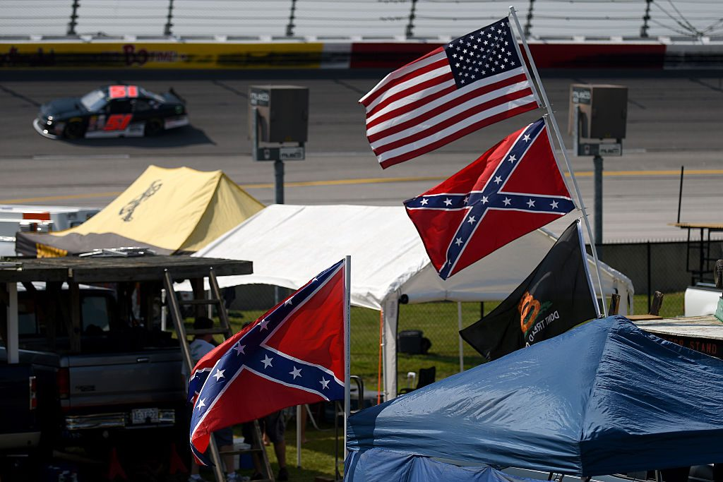 Confederate flags flying with American flags inside of NASCAR track
