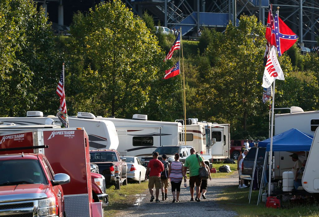 NASCAR fans walk past a pair of Confederate flags and a Trump flag as they make their way to the Bass Pro Shops NRA Night Race in Bristol, TN