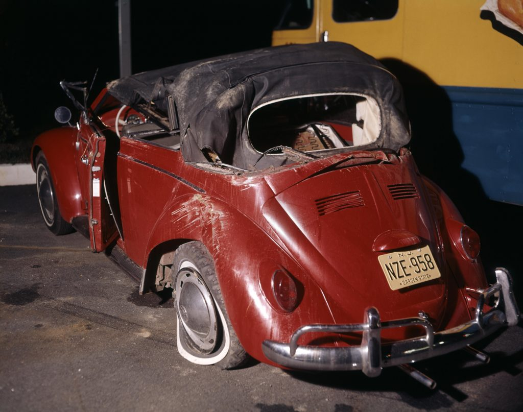 A red VW convertible after a roll-over crash sitting in a lot