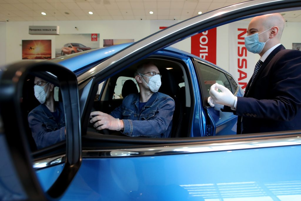 A customer and dealership employee with masks discuss a car in a showroom.
