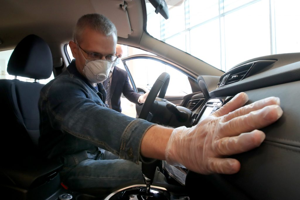 COVID-19 precautions. A customer wears a mask and examines a car in a showroom.