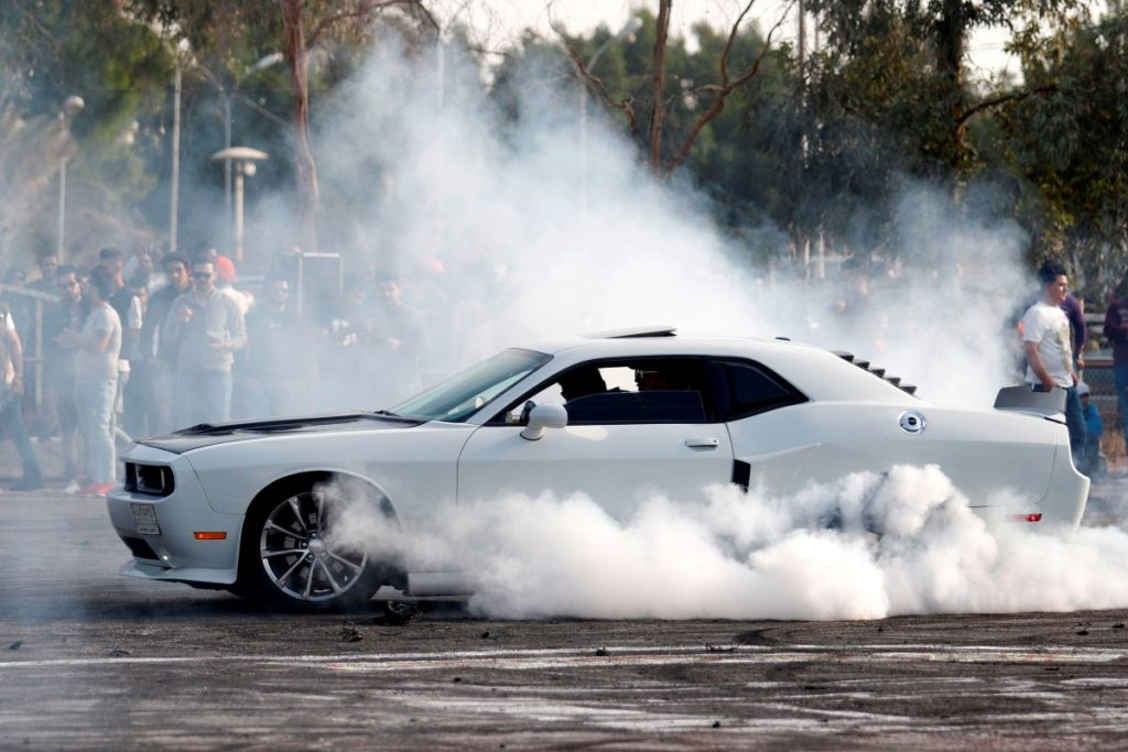 The driver of a white Dodge Challenger performs a burnout
