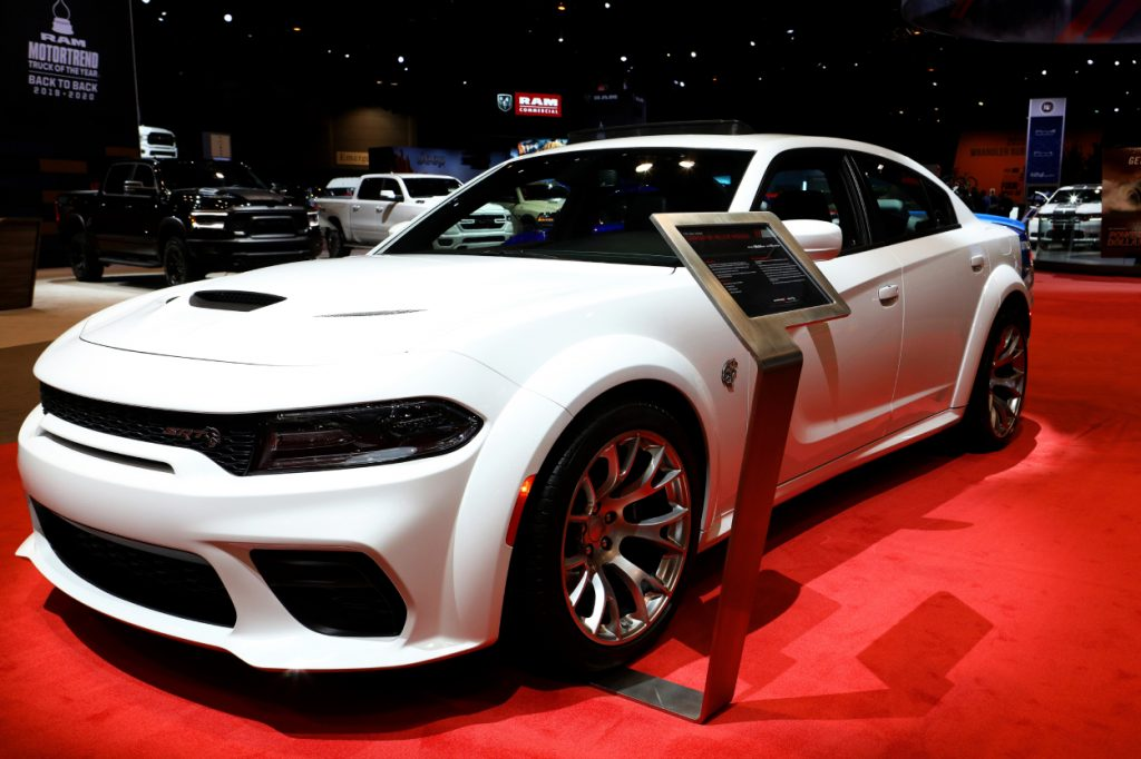 A white Dodge Charger on display at an auto show